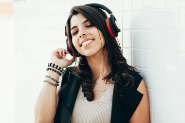 Young beautiful woman using headphone listening to music outdoor
