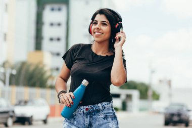 Beautiful young woman using headphone listening to music and dri