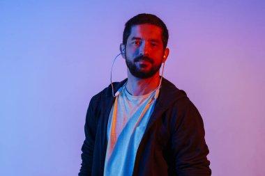 Neon light portrait of bearded man in earphones. Listening to music