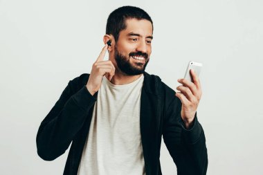 Portrait of a young bearded man wearing sports clothes and wireless earphones.