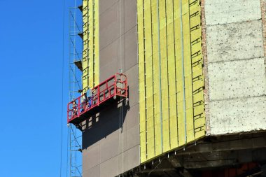 High-altitude work on the external walls of glass wool insulation. Workers use special equipment to insulate the facade of the building and finish it with panels