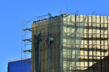 High-altitude work on the external walls of glass wool insulation. Workers using the scaffolding and special equipment perform the insulation of the facade of the building