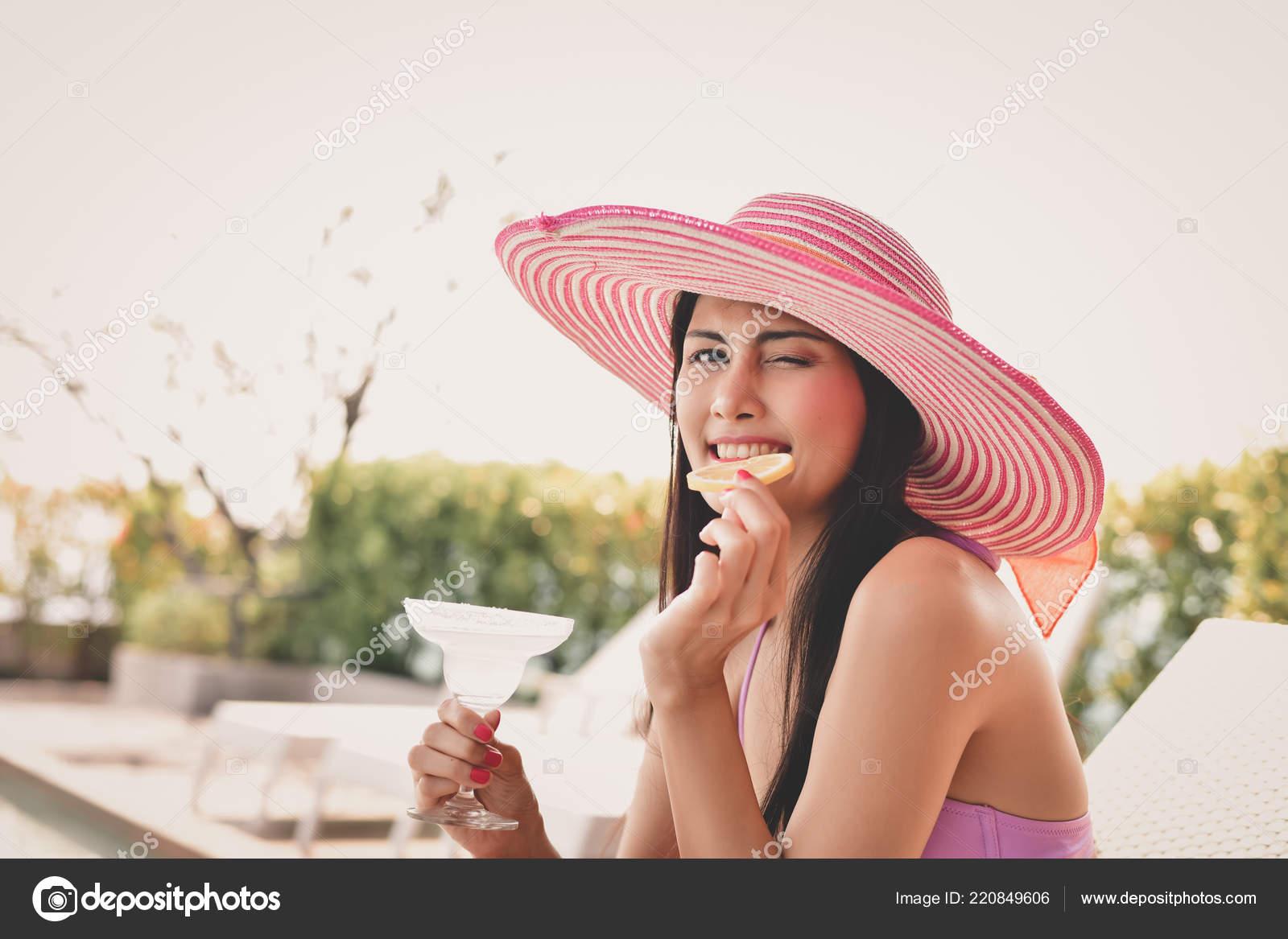 Beautiful girls in swimwear are drinking. Asian girls drink fruit juice at  the pool. Beautiful girl in swimwear is happy at the pool.