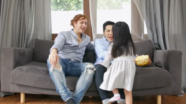 Family concept. A young girl is watching a movie with a gay family.