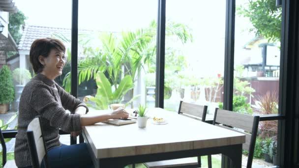 Obchodní koncepty. Žena středního věku čeká, až se zákazníci setkají v kavárně. Rozlišení 4k.