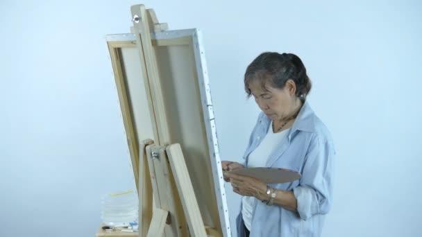 Künstlerkonzept. Eine Frau mittleren Alters mischt Farben auf einem Teller auf weißem Hintergrund. 4k-Auflösung.
