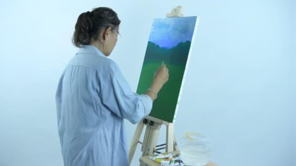 Künstlerkonzept. eine Frau mittleren Alters, die in einem Atelierraum zeichnet. 4k-Auflösung.