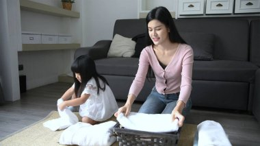 Holiday concept. The daughter is helping her mother fold the clothes into the basket. 4k Resolution.