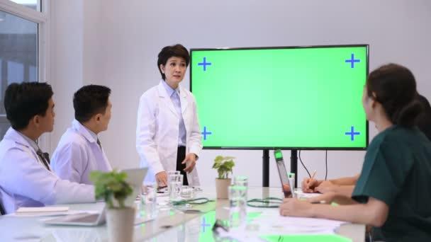 Medizinkonzept. Der Arzt präsentiert die Arbeit auf dem grünen Monitor. 4k-Auflösung.