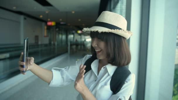 Tourismuskonzept. Eine Asiatin macht ein Foto auf dem Flughafen. 4k-Auflösung.