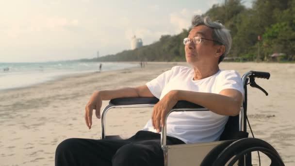 Zakázaný koncept. Na kolečkovém křesle u pláže sedí starý Asiat. Rozlišení 4k.