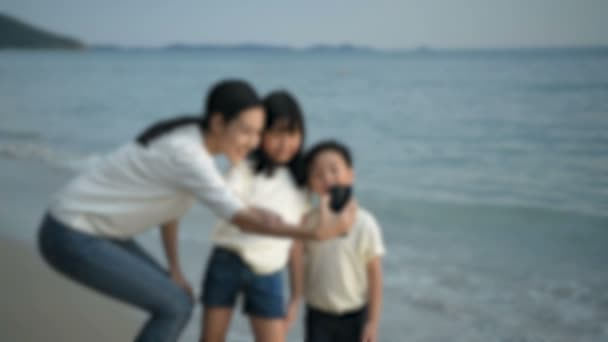 Holiday concept. Mother and children are taking pictures together on the beach. 4k Resolution.