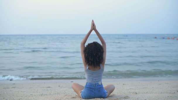 Ünnepi ötlet. Gyönyörű lány jógázik a parton. 4k felbontás.