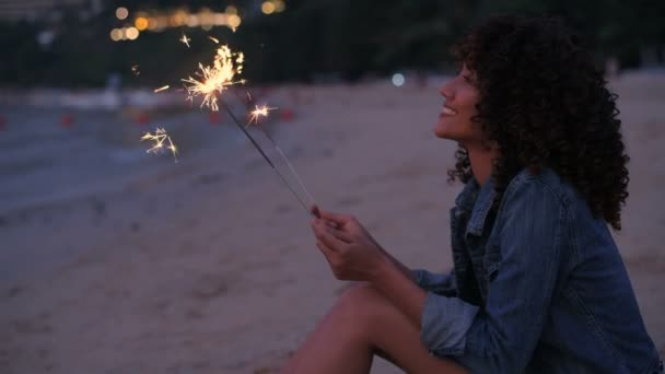 Holiday concept. A beautiful woman playing fireworks on the beach. 4k Resolution.