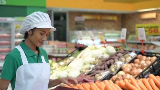 Nákupní koncepce. Ta holka přidává ovoce a zeleninu do regálů v obchoďáku. Rozlišení 4k.