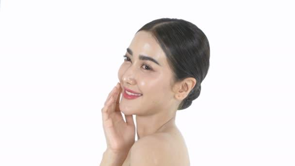 Szépség koncepció. Egy gyönyörű nő gyengéden simogatja az arcát egy fehér háttéren. 4k felbontás.