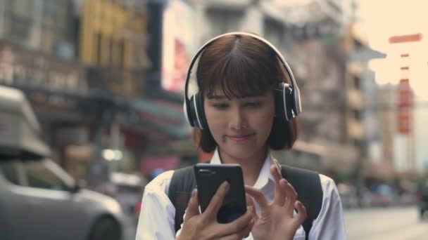 Tourism concept. Asian women are choosing songs to listen to from mobile phones. 4k Resolution.