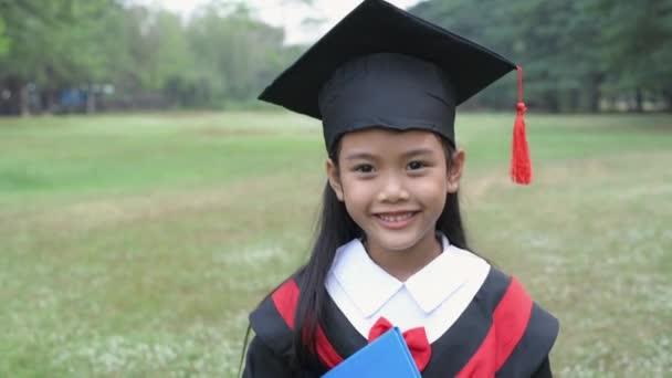 Oktatási koncepciók. Egy ázsiai lány általános iskolai egyenruhában sétál a kertben. 4k felbontás.