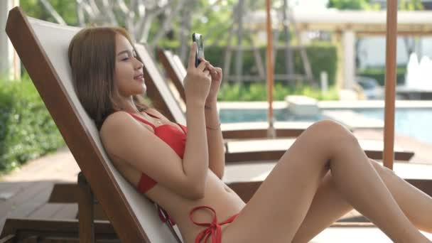 Holiday concept. A beautiful woman playing with a mobile phone by the pool. 4k Resolution.