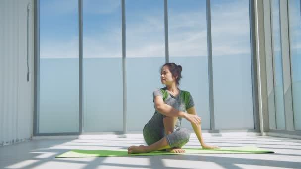 Pojem cvičení. usmívající se žena natahuje nohu na podložku v tělocvičně. Rozlišení 4k.