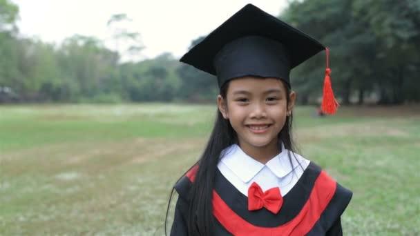 Oktatási koncepciók. A lány, aki a ballagási ruhát viseli, boldog a kertben. 4k felbontás.
