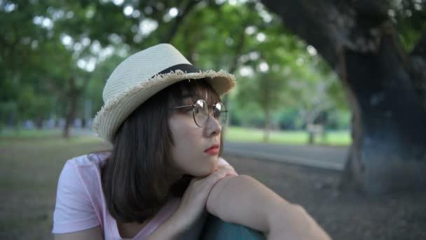 Ferienkonzept. Ein asiatisches Mädchen sitzt einsam auf einer Bank im Garten. 4k-Auflösung.