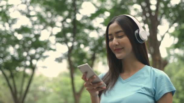 Ferienkonzept. Das Mädchen hört die Musik im Park. 4k-Auflösung.