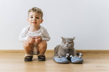 cute little boy and grey british shorthair cat in sleepers at home