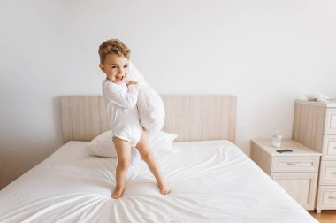 adorable toddler boy in white bodysuit playing with pillow on bed at home