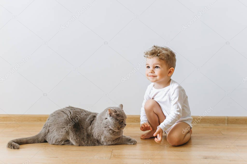cute little child in white bodysuit and grey british shorthair cat resting on floor at home