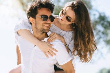 portrait of boyfriend giving piggyback to girlfriend