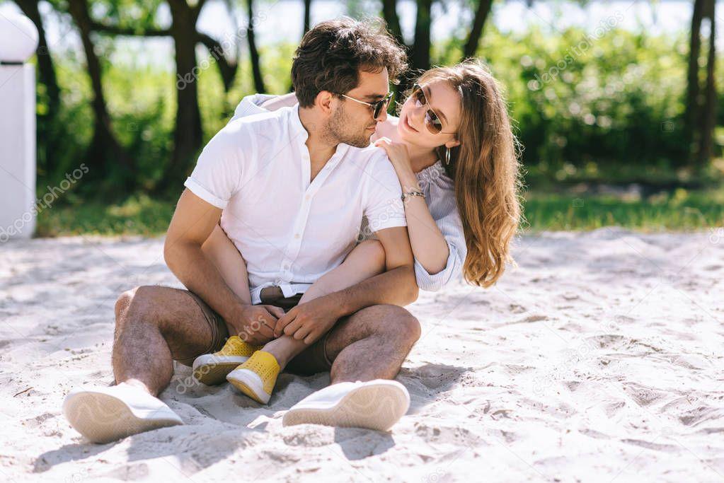 attractive girlfriend hugging boyfriend on sandy city beach