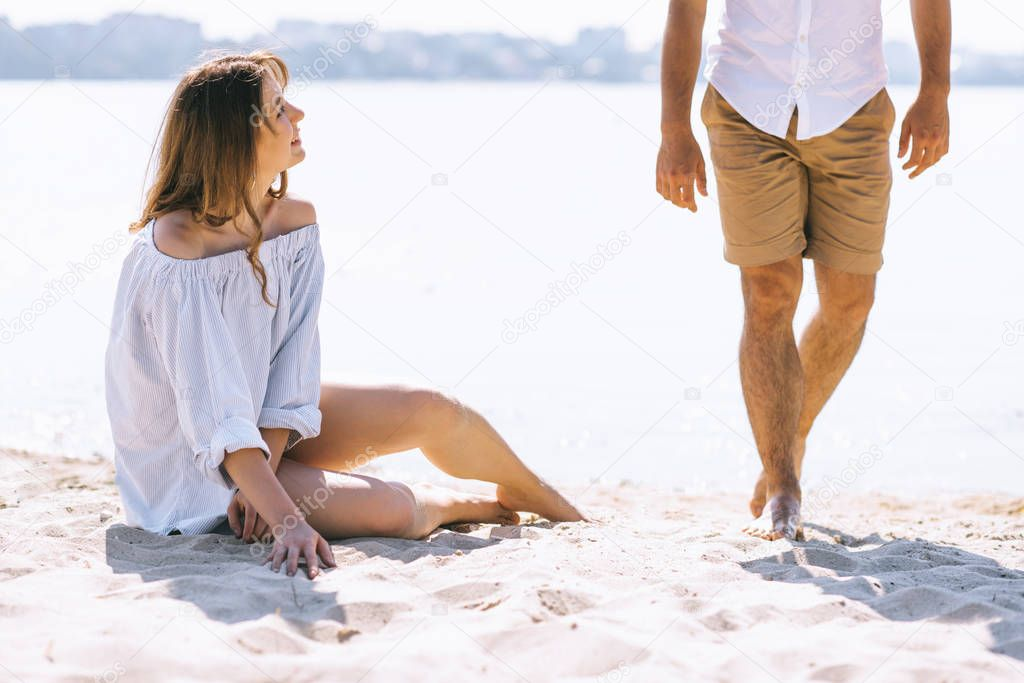 cropped image of girlfriend sitting on sandy city beach near river and looking at boyfriend