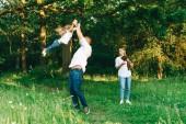 Fotografie glückliche Familie mit Tochter und kleinen Labrador Welpen im Wald