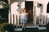 Photo Little kid standing on porch of country house alone on summer day