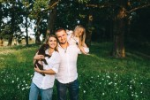 Photo portrait of smiling parents with daughter and little labrador puppy in forest