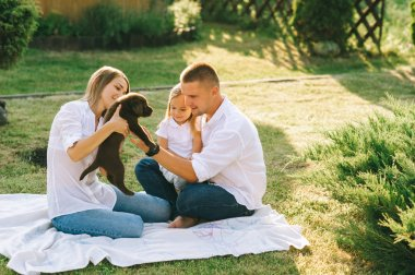 parents with little daughter and labrador puppy resting together on backyard