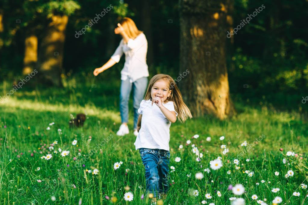 selective focus of smiling kid running with mother standing behind in forest