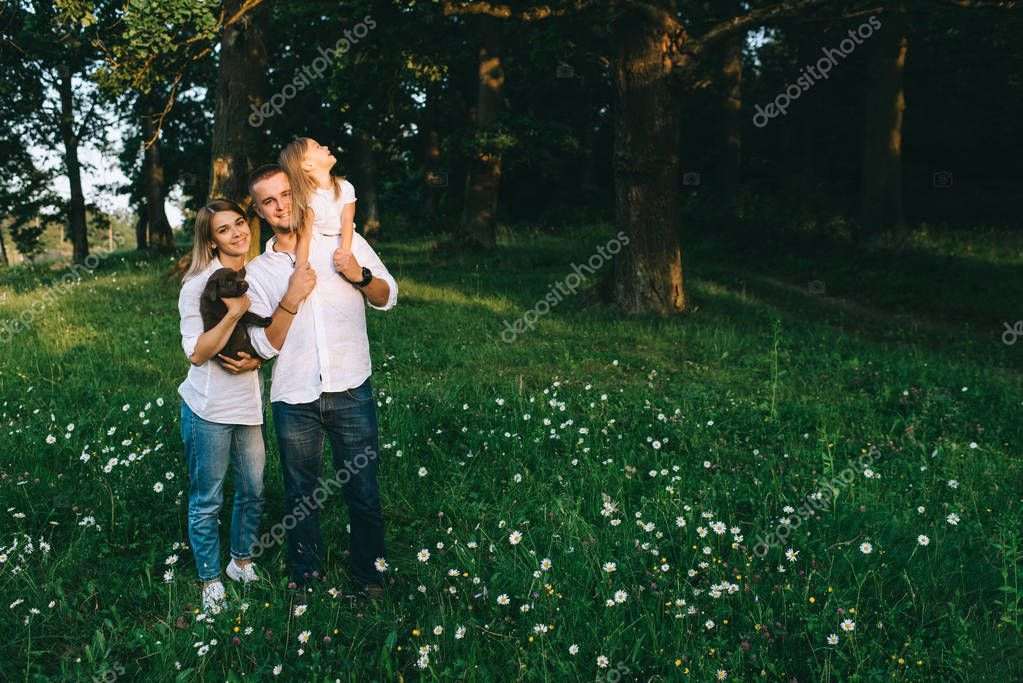 smiling parents with daughter and little labrador puppy in forest