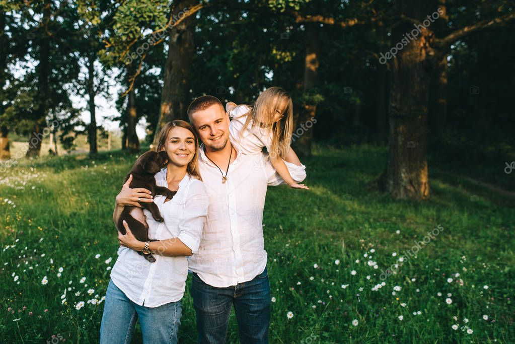 portrait of smiling parents with daughter and little labrador puppy in forest