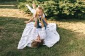 Fotografia madre e piccola figlia sveglia che ha divertimento insieme sul cortile