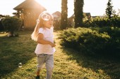 kis gyerek szórakozik a szappanbuborékok kertben