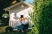 Fényképek Mosolyogva család kis gyermekével együtt ültek a verandán a kis vidéki ház