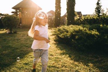 little kid having fun with soap bubbles on backyard