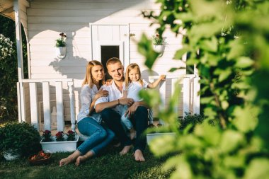 Smiling family with little child sitting together on porch of little country house