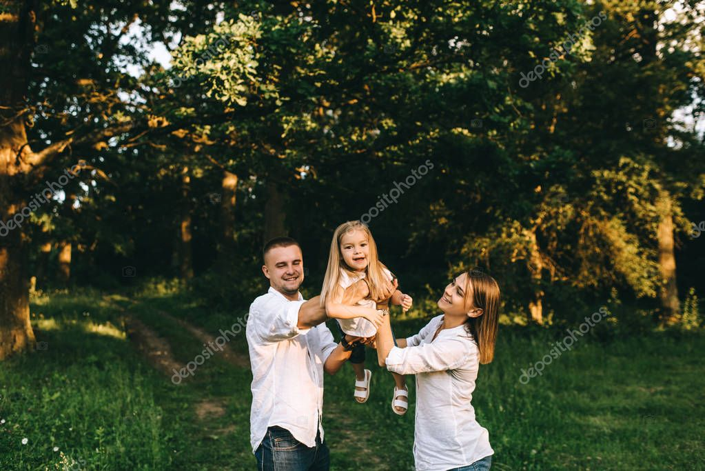 portrait of family having fun together in forest on summer day