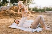Šťastný otec drží malého syna při odpočinku na seno v obci