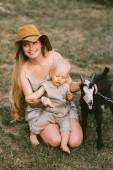 Fotografie Maminka v klobouku, malý syn a domácí koza na zelené trávě na venkově