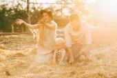 šťastní rodiče a malého syna v lněné oděvy na seno v krajině