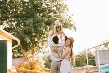 back view of woman standing near husband with son on hands at countryside